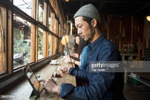 Hombre de mediana edad usando una tableta digital en Café