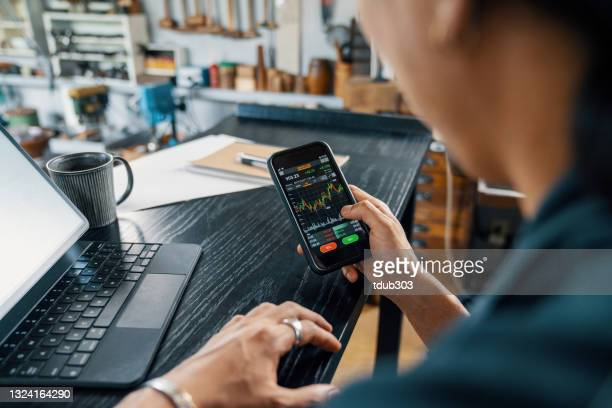 mid adult man using a smart phone to monitor his cryptocurrency and stock trading - stock market stock pictures, royalty-free photos & images