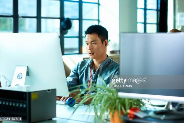 mid adult man using computer and concentrating - desktop pc stock pictures, royalty-free photos & images