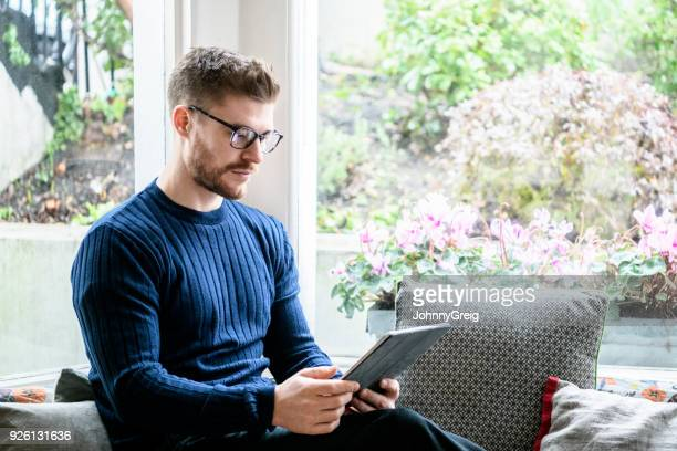 Mid adult man using digital tablet at home