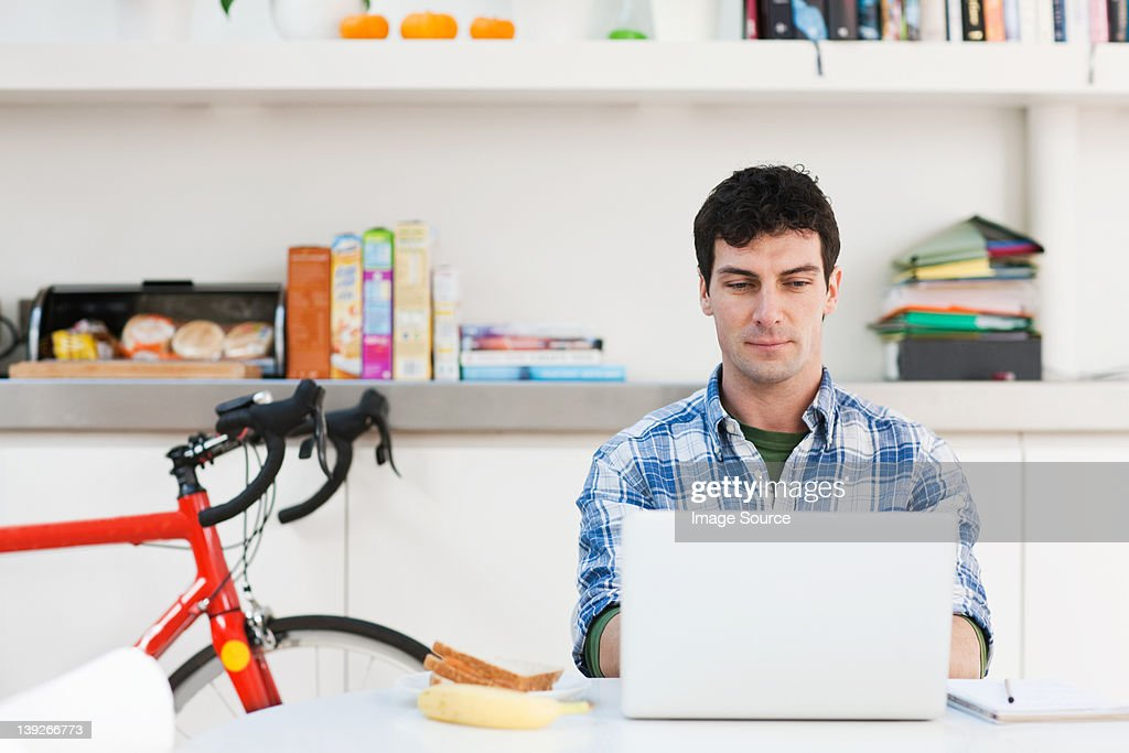 Mid adult man using laptop at home : Stock Photo