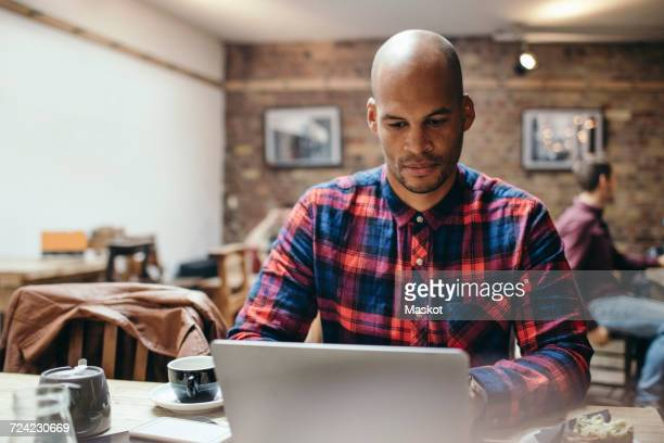 Mid adult man using laptop at table in coffee shop