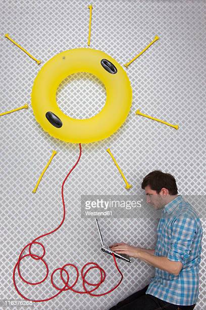 Mid adult man using laptop connected to sun shape float