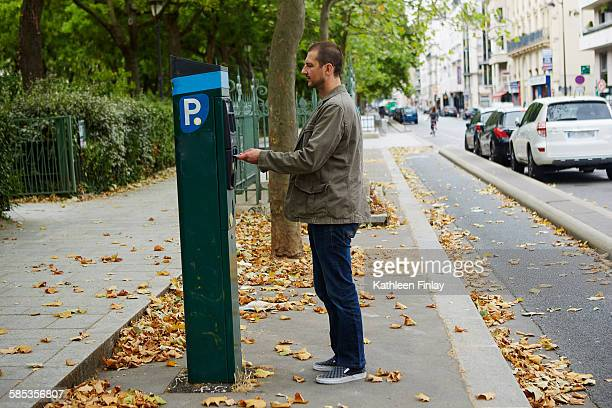 mid adult man using parking meter in street - parking meter stock photos and pictures