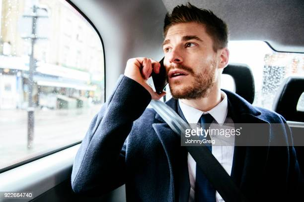 Mid adult man using smartphone in back of cab
