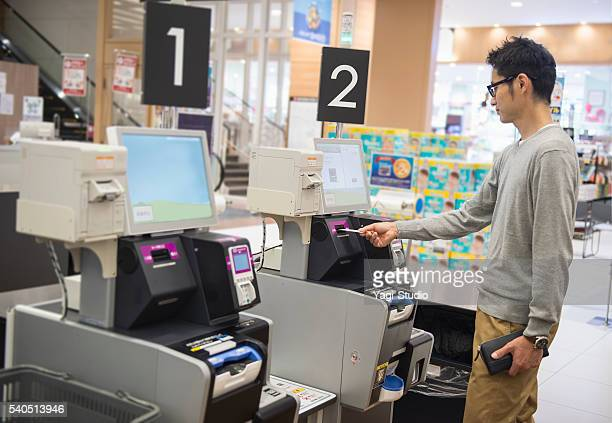 Mid Adult man using the cash register of self-service