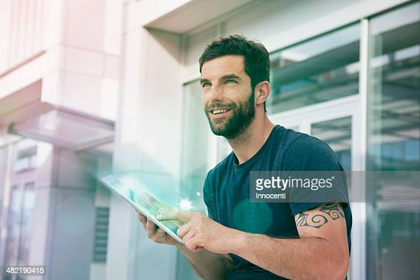 Mid adult man using touchscreen on digital tablet with lights