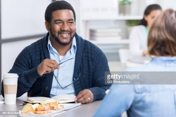 Mid volwassen man bezoeken met collega tijdens de lunchpauze