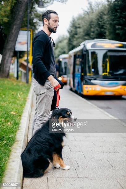 Mid adult man waiting with pet dog at city sidewalk