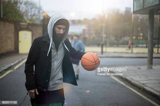 Mid adult man walking along street, bouncing basketball