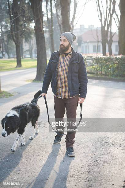 Mid adult man walking dog through park