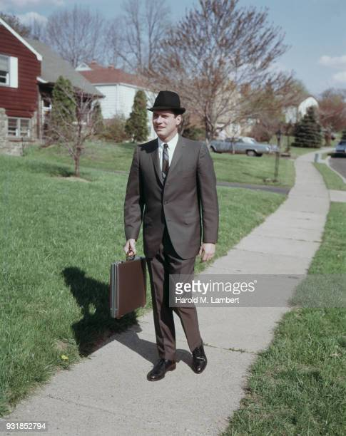 Mid adult man walking in park with briefcase
