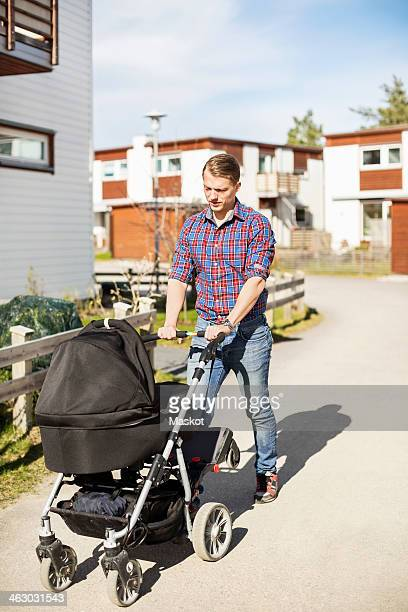 Mid adult man walking with baby carriage on sunny street