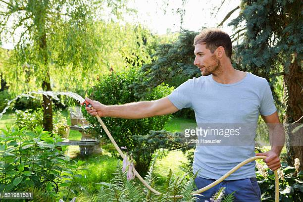 Mid adult man watering garden with hosepipe