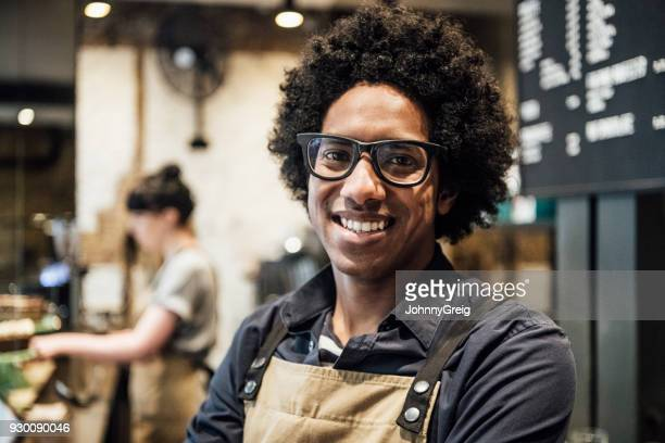 Mid adult man wearing glasses smiling and woking in cafe