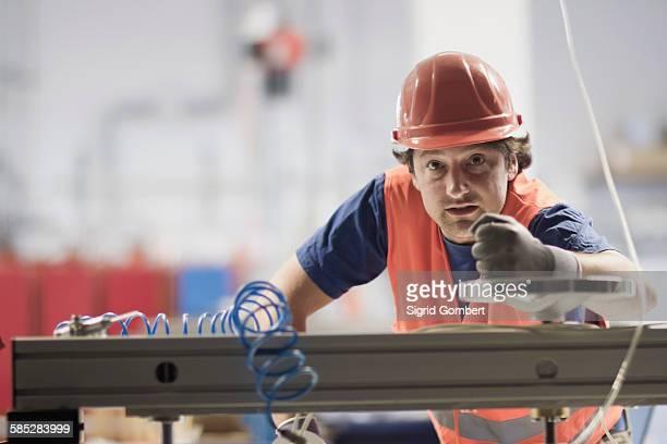 mid adult man wearing hard hat looking at camera, operating machine - sigrid gombert fotografías e imágenes de stock