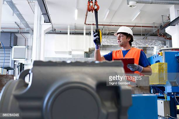 mid adult man wearing hard hat operating machine, holding clipboard - sigrid gombert photos et images de collection