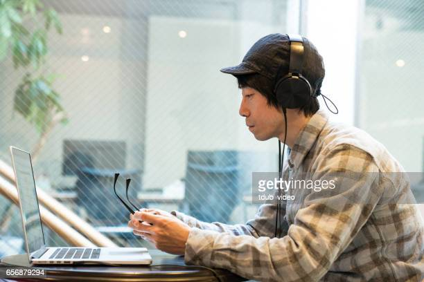 Mid adult man wearing headphones and working on a computer in a public space