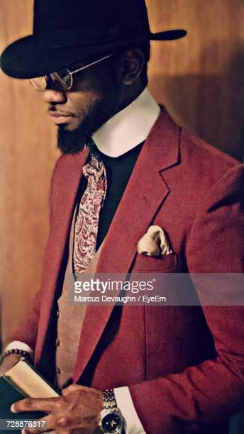 mid adult man wearing red suit against wall - red suit stock pictures, royalty-free photos & images