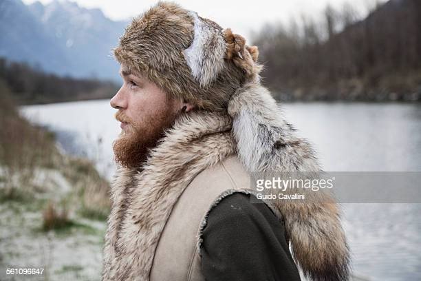 mid adult man wearing trapper hat, portrait - hairy man stock pictures, royalty-free photos & images