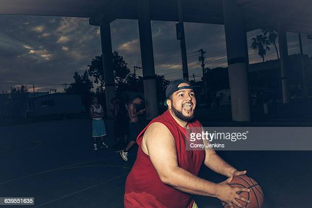 mid adult man wearing vest playing basketball open mouthed smiling - chubby men stock photos and pictures