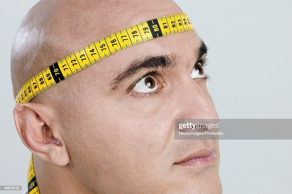 Mid adult man with a measuring tape around his head : Stock Photo