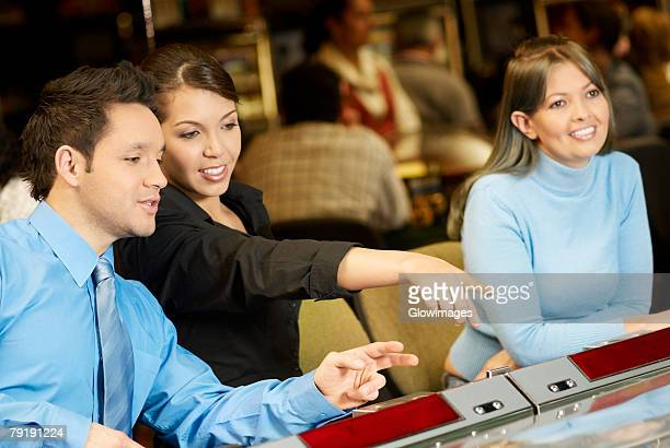 mid adult man with a teenage girl and a young woman in a casino - teen pokies stock photos and pictures