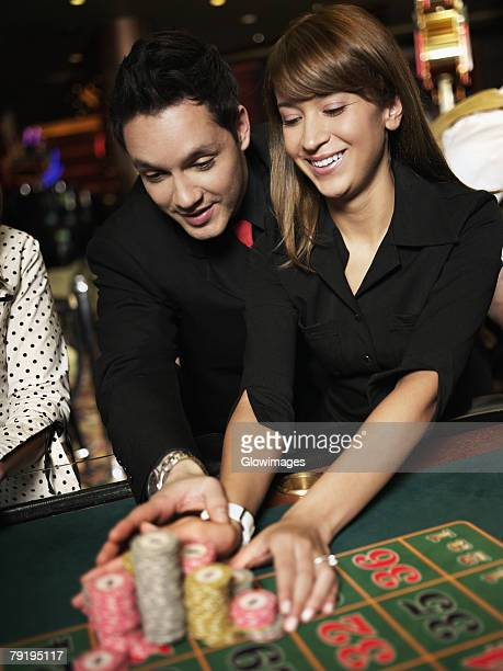 Mid adult man with a young woman placing gambling chips on a gambling table