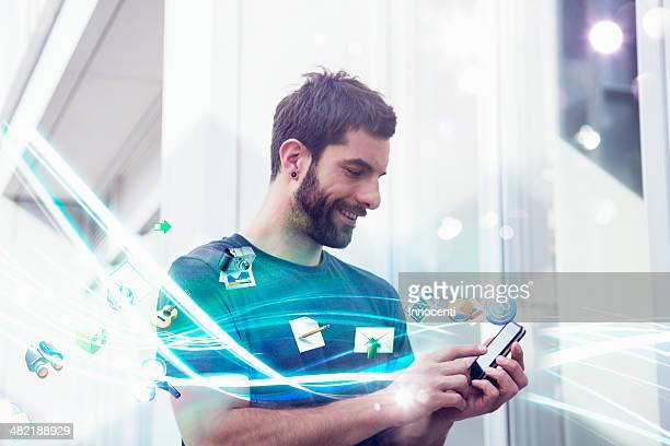 mid adult man with apps and lights coming from smartphone - data stream stock photos and pictures