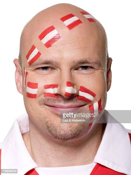Man with Austrian flag painted on face, smiling, close-up, portrait