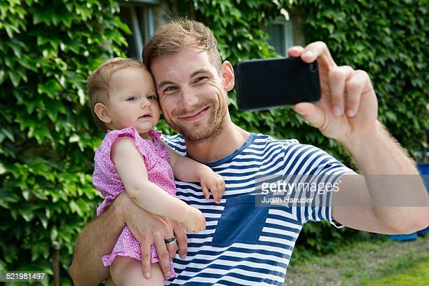 Mid adult man with baby daughter taking selfie on smartphone in garden