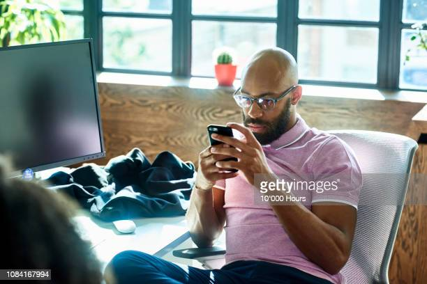 mid adult man with beard and glasses texting in office - westeuropa stock-fotos und bilder