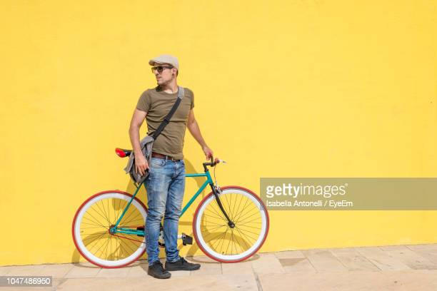 mid adult man with bicycle standing against yellow wall - building feature stock pictures, royalty-free photos & images