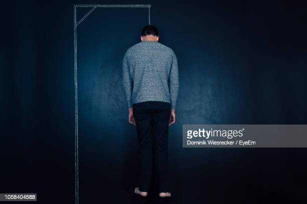 mid adult man with chalk drawing on blackboard - hanging death photos stock pictures, royalty-free photos & images