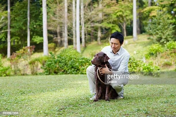 mid adult man with chocolate labrador in park - イヌ科 ストックフォトと画像