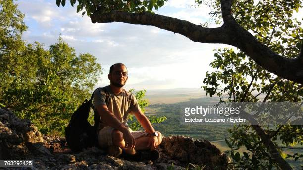 Mid Adult Man With Cross-Legged Sitting On Rocks Against Cloudy Sky