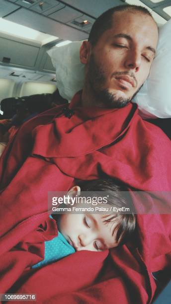 Mid Adult Man With Daughter Sleeping In Seat In Airplane