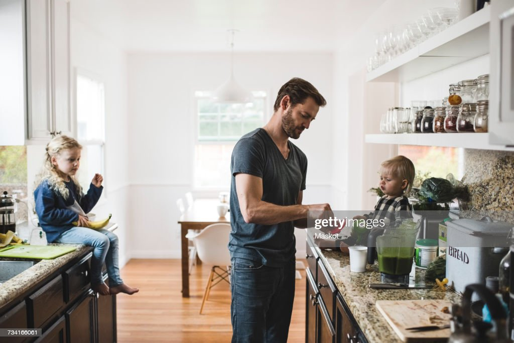 Mid adult man with daughters cooking food in kitchen at home : Stock Photo