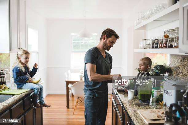 Mid adult man with daughters cooking food in kitchen at home