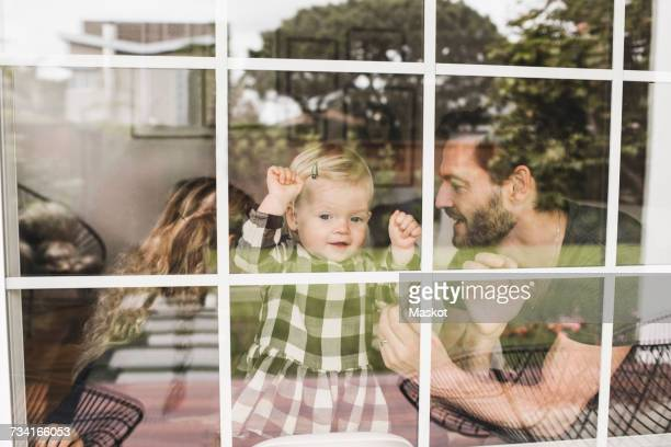mid adult man with daughters seen through window of home - photographed through window stock pictures, royalty-free photos & images