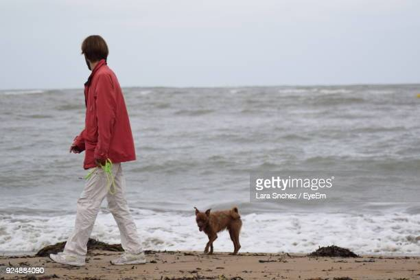 Mid Adult Man With Dog Walking At Beach Against Sky