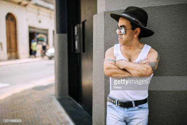 mid adult man with dwarfism wearing cowboy hat on the street - dwarf man stock pictures, royalty-free photos & images