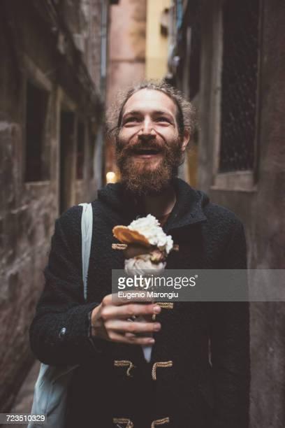 mid adult man with gelato in dark alley, venice, italy - coat foto e immagini stock