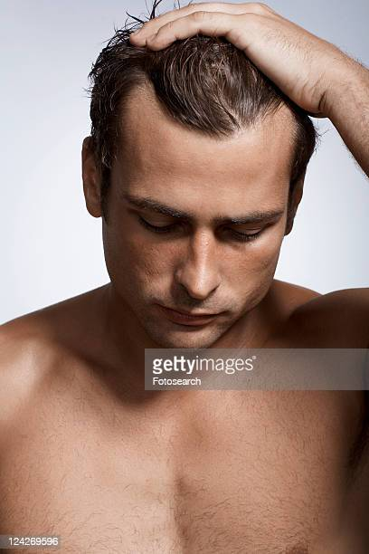 Mid adult man with hand in his hair