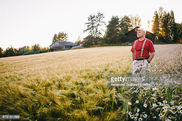 Mid Adult Man With Hands In Pockets Standing On Wheat Field