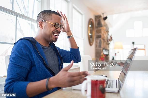 Mid adult man with hands raised in disbelief using laptop at kitchen counter