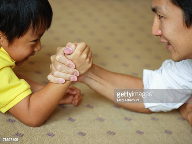 Mid adult man with his son arm wrestling
