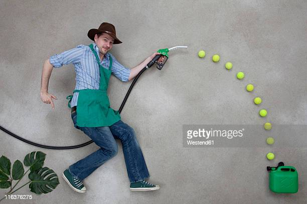 Mid adult man with hose fuelling into green canister