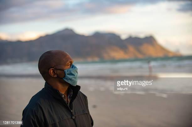 homme adulte moyen avec le masque sur la plage et le fond de montagne regardant loin - hommes d'âge moyen photos et images de collection