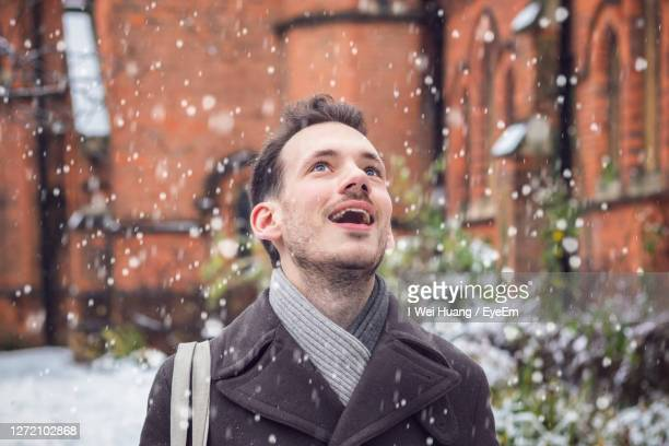 mid adult man with mouth open looking up during snowfall - snow stock pictures, royalty-free photos & images